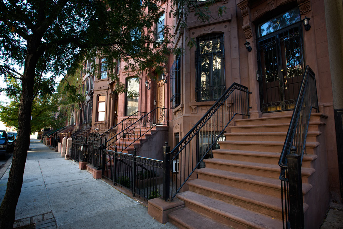 Photo of a row of quintessential brownstones — Harlem, New York